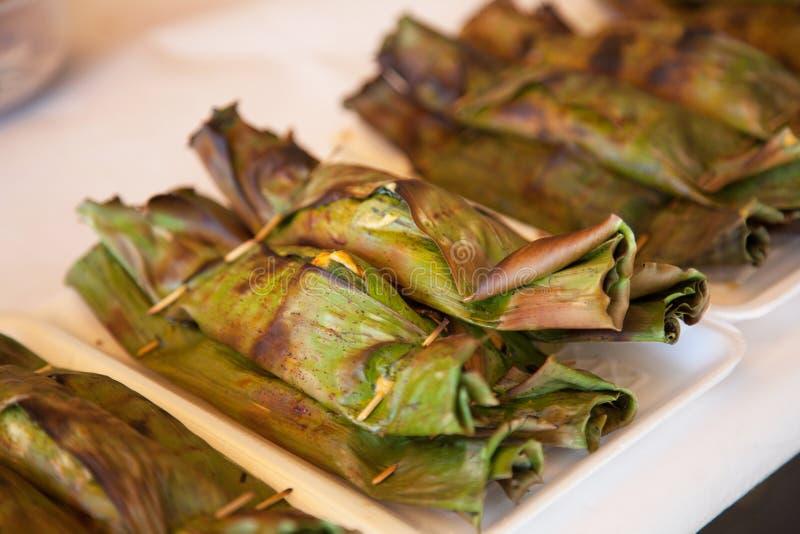 烤被蒸的海鲜咖喱鱼、虾和乌贼在香蕉包裹的椰奶蛋糕离开 传统烤泰国海 免版税库存图片