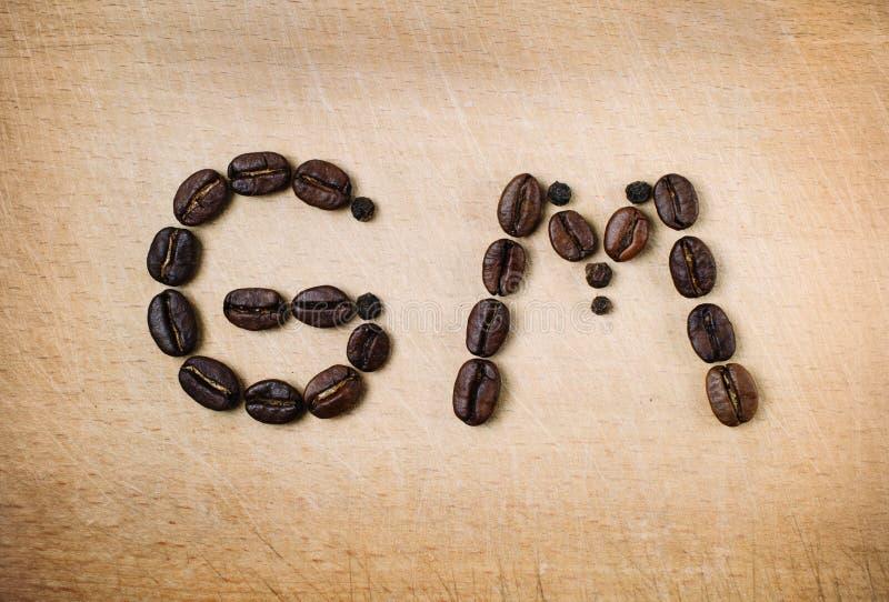 烤豆在早晨好组合形状被设置  信件由在木背景的咖啡种子形成了 关闭 免版税库存图片