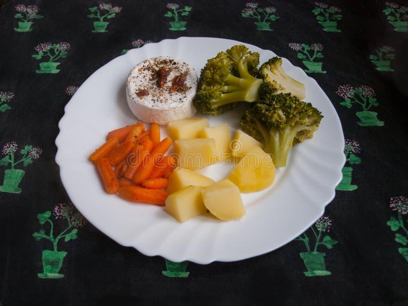烤软制乳酪用在白色板材的辣椒用土豆、红萝卜和硬花甘蓝 库存照片