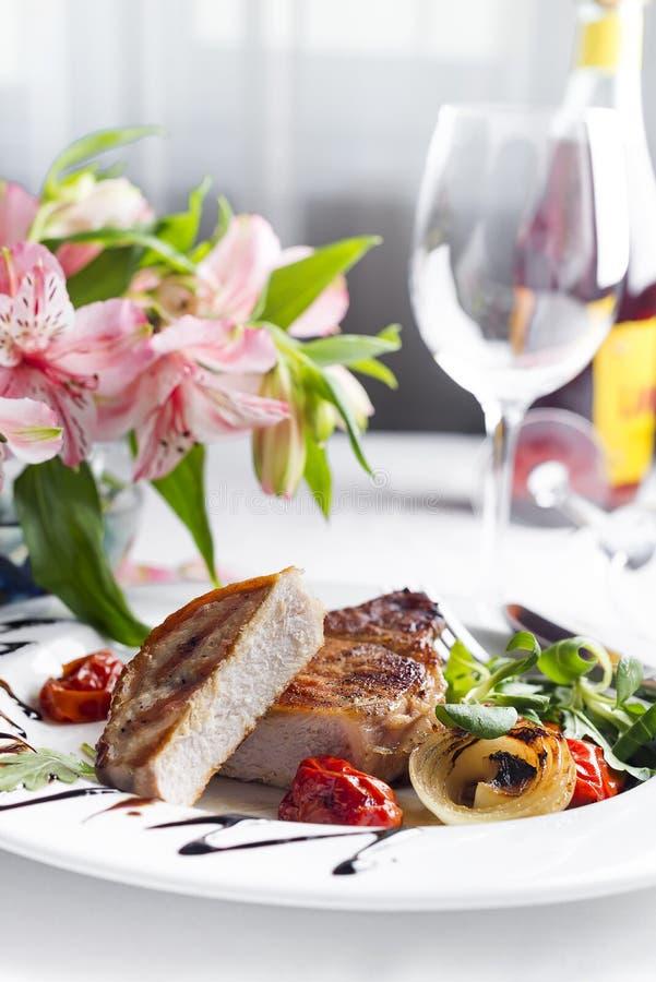 烤里脊肉牛排的多汁重水多的部分服务用蕃茄和烘烤菜 免版税图库摄影