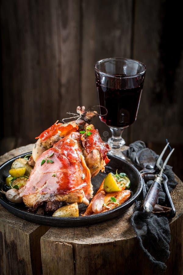 烤野鸡用烟肉和菜在黑暗的背景 免版税库存照片