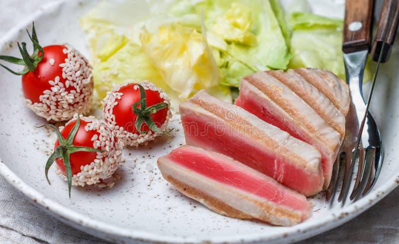烤金枪鱼用香料、西红柿、芝麻和莴苣 图库摄影