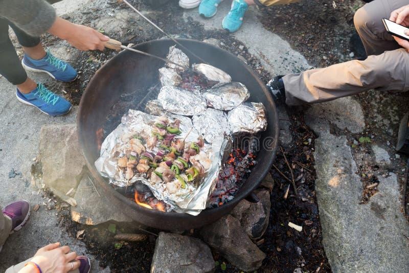 烤食物的朋友在Firepit在森林在远足期间 库存图片