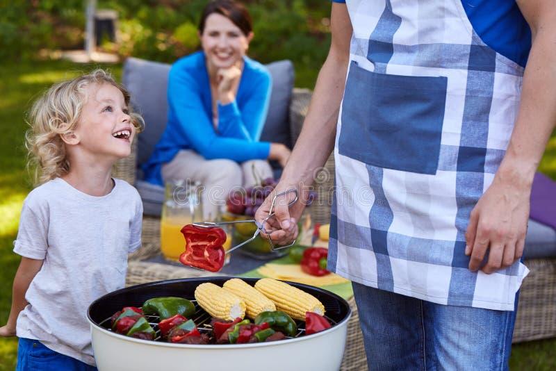 烤食物的父亲和孩子 库存图片