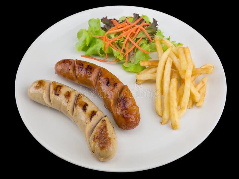 烤香肠牛排服务用炸薯条和沙拉 免版税图库摄影