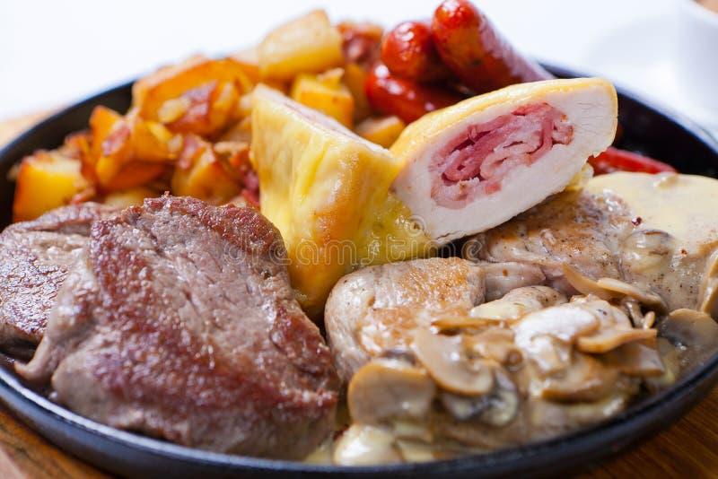 烤香肠用土豆、蘑菇和烤鸡在格栅平底锅 库存图片
