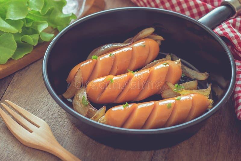 烤香肠用在煎锅的葱 免版税库存照片