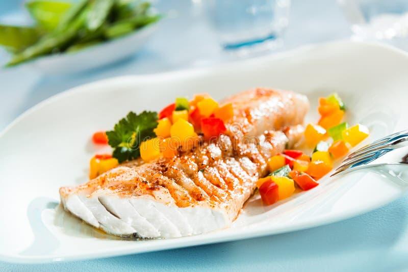 烤鱼片用五颜六色的新鲜的沙拉 免版税库存照片