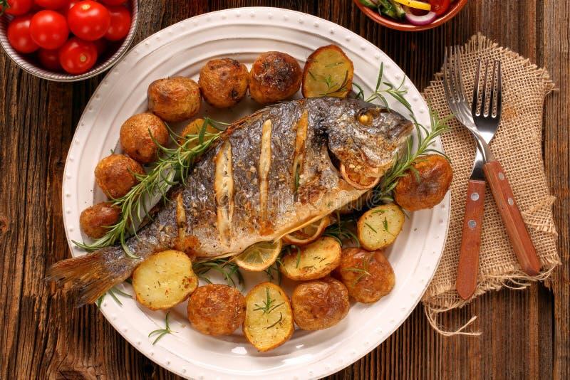 烤鱼用烤土豆和菜在板材 库存图片