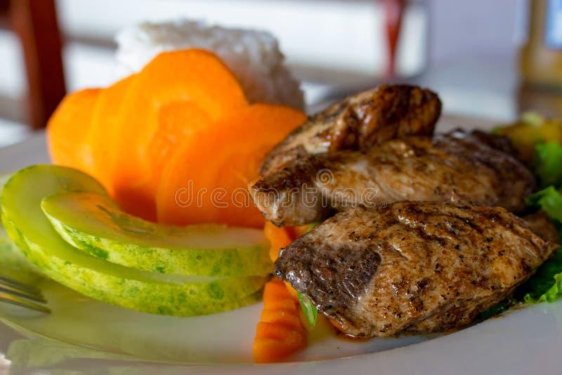 烤鱼用白米和新鲜蔬菜 亚洲烹调概念 与黄瓜切片和红萝卜的烤鲑鱼排 免版税库存图片