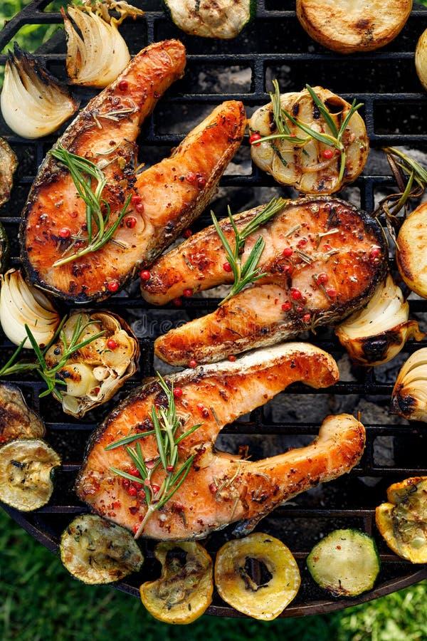 烤鱼,烤了鲑鱼排增加迷迭香、芳香香料和菜在格栅板材户外 库存照片