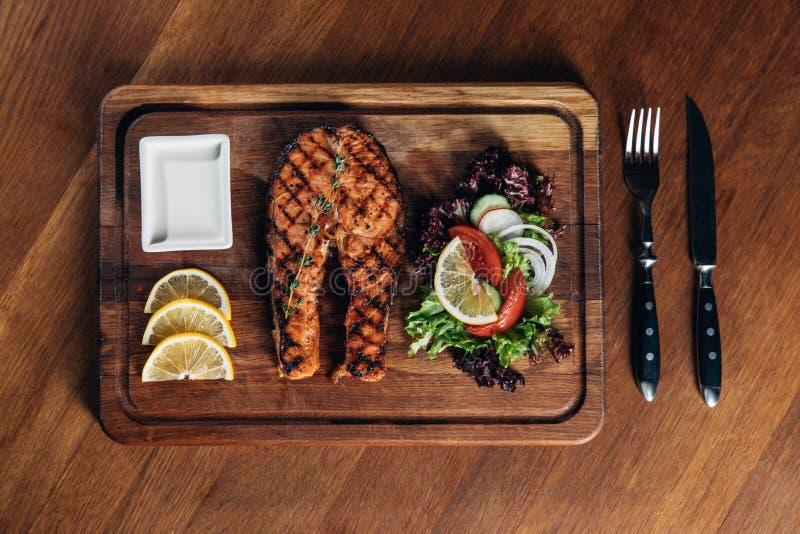 烤鲑鱼排在有柠檬切片和沙拉的木板服务 库存图片