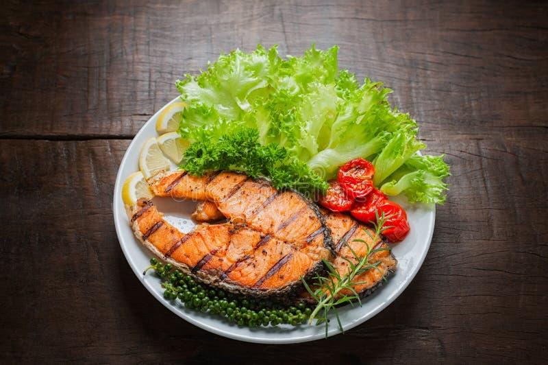 烤鲑鱼排服务用烤蕃茄,沙拉,切的柠檬,胡椒种子,迷迭香,荷兰芹 库存照片