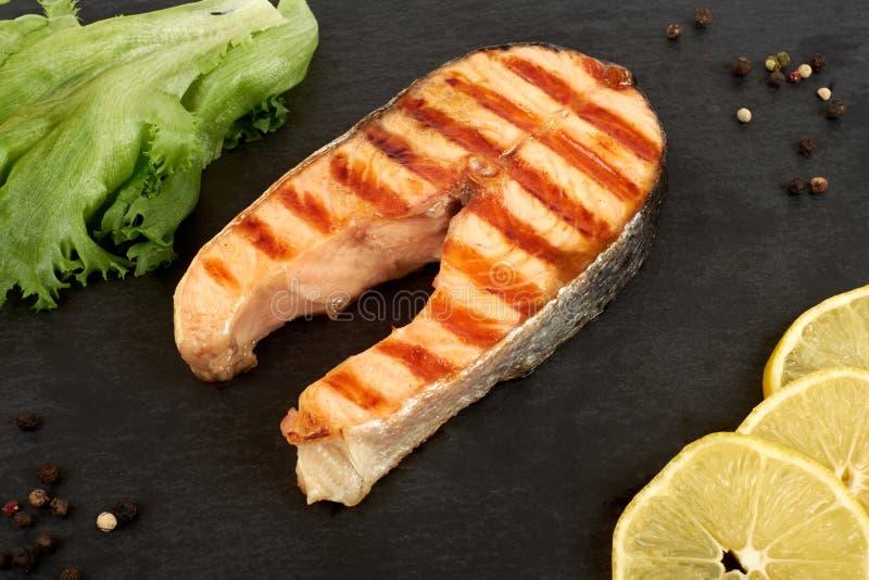 烤鲑鱼排用柠檬和沙拉在板岩板材 免版税库存图片