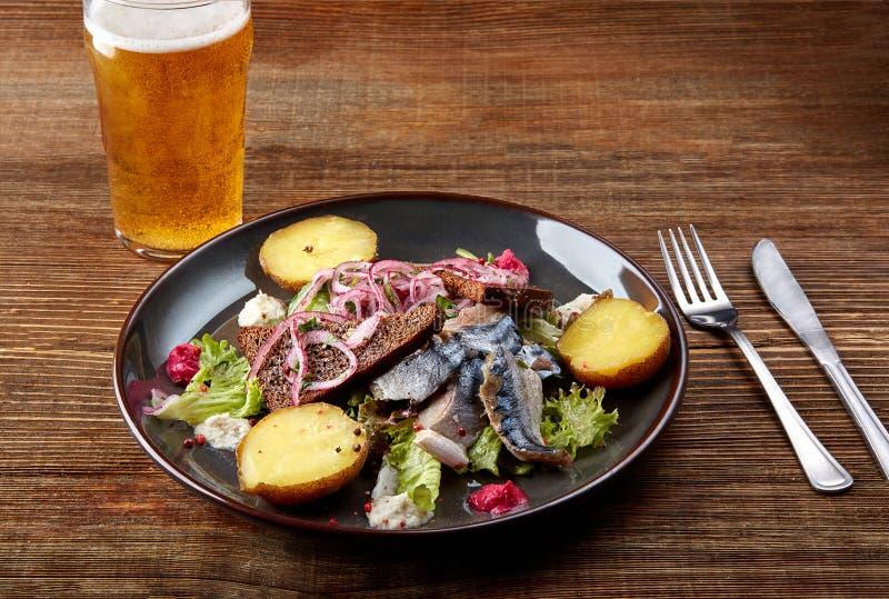 烤鲭鱼鱼用在木桌上的被烘烤的土豆 库存图片