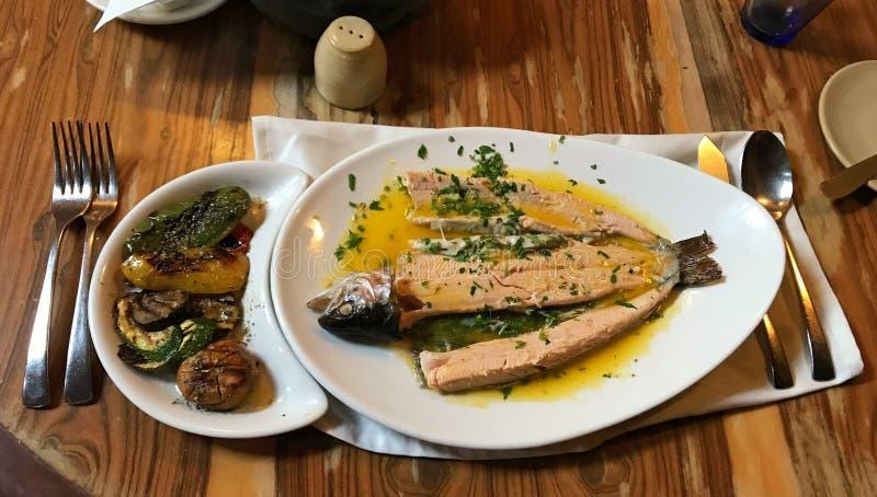 烤鳟鱼用在木桌上的调味汁和莳萝草本 库存照片