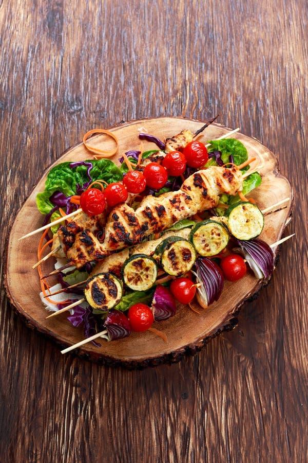 烤鸡内圆角kebab用樱桃在BBQ烤了 蕃茄、夏南瓜和红洋葱在竹棍子 免版税库存照片