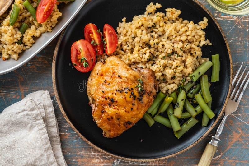 烤鸡大腿用碾碎干小麦、芦笋豆和蕃茄 可口午餐 复制空间 免版税库存照片