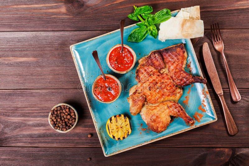 烤鸡或火鸡用香料、柠檬、西红柿酱、蓬蒿和皮塔饼面包在板材在黑暗的木背景 感恩 免版税库存照片