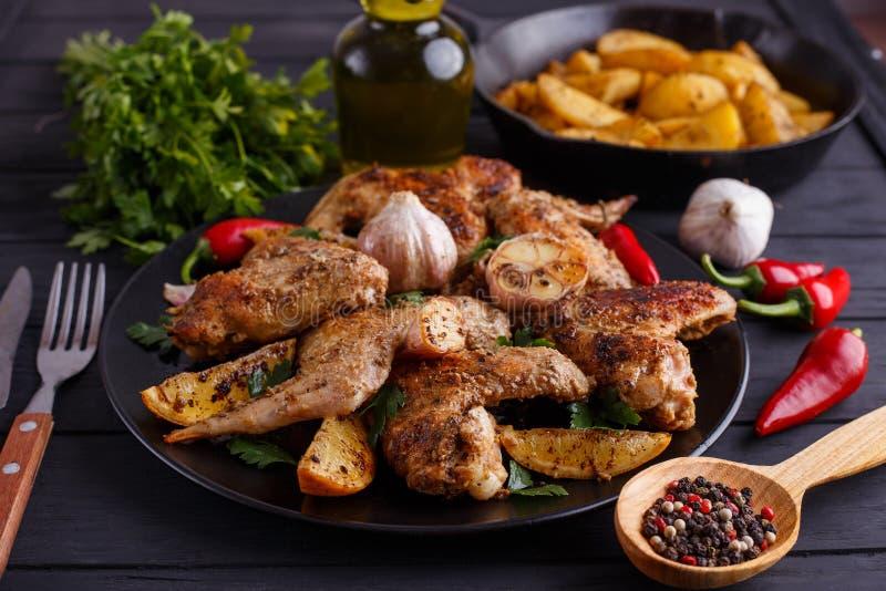 烤鸡翼、被烘烤的土豆、草本和香料在kitch 库存图片