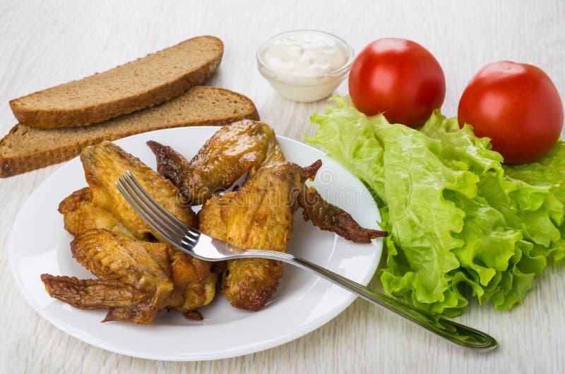烤鸡翼,在板材,蕃茄,面包, mayonnais的叉子 免版税库存图片
