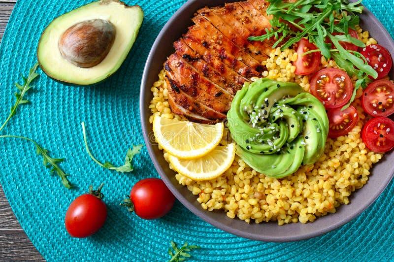 烤鸡胸脯、新鲜蔬菜、鳄梨、芝麻菜 在木桌上吃节食午餐 健康食品 顶视图 免版税库存图片