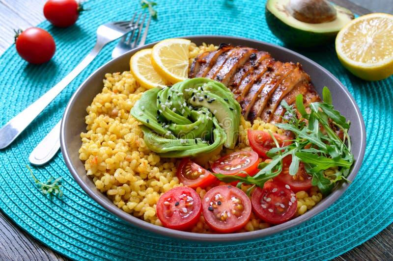 烤鸡胸脯、新鲜蔬菜、鳄梨、芝麻菜 在木桌上吃节食午餐 健康食品 免版税库存照片