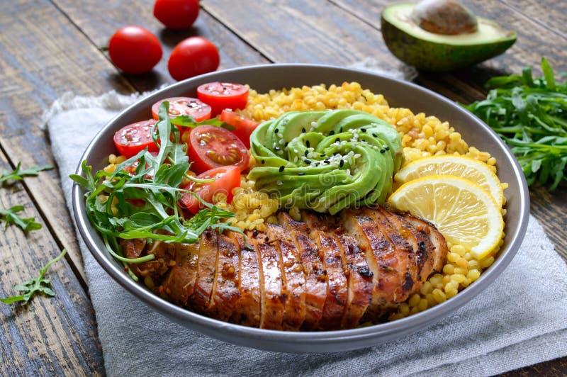 烤鸡胸脯、新鲜蔬菜、鳄梨、芝麻菜 在木桌上吃节食午餐 健康食品 免版税库存图片