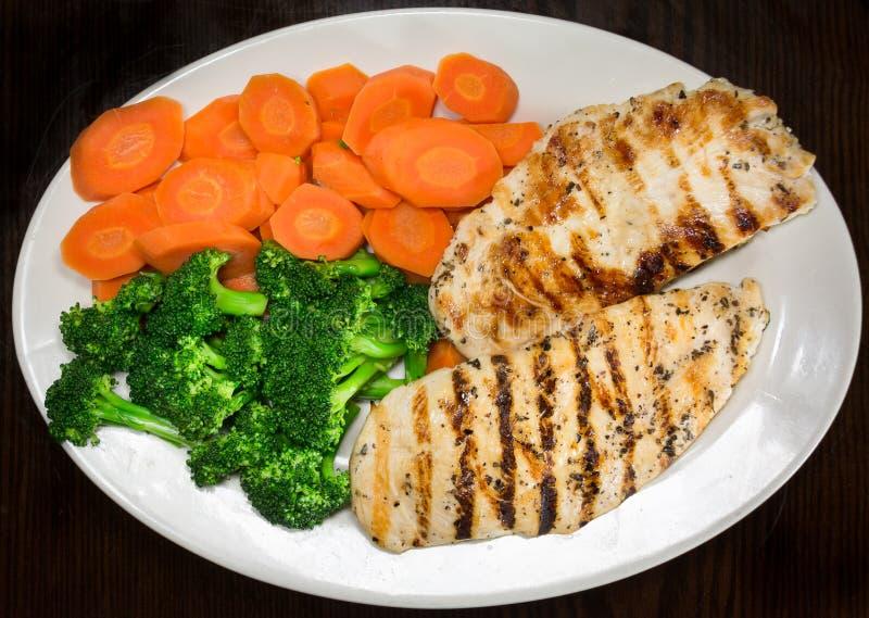 烤鸡胸脯、硬花甘蓝和红萝卜在板材 免版税图库摄影