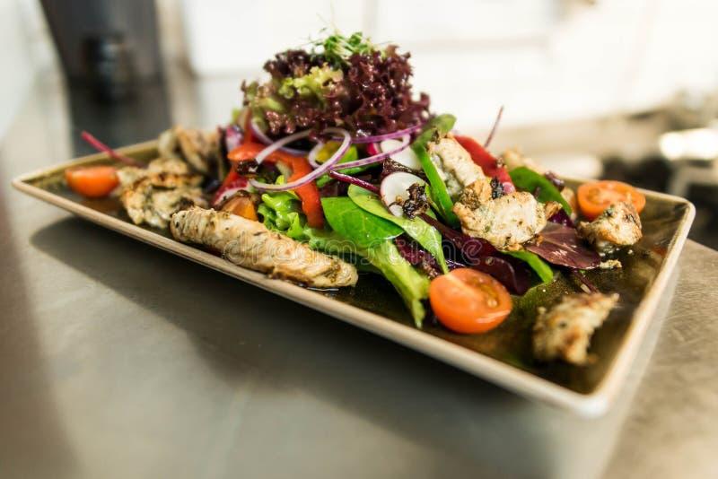 烤鸡胸脯内圆角用新鲜的蕃茄菜沙拉 厨师做的概念健康食物在厨房里 库存图片