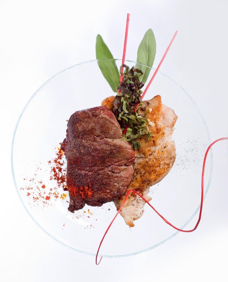 烤鸡胸脯和炸猪排用牛肉肉牛排和草本在透明板材 免版税库存图片