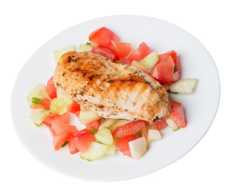 烤鸡胸脯沙拉用蕃茄、黄瓜和葱 在白色背景隔绝的板材的烤鸡胸脯 免版税库存图片