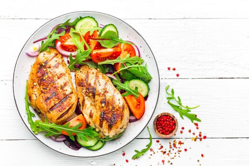 烤鸡胸脯炸鸡内圆角和蕃茄、黄瓜和芝麻菜叶子新鲜蔬菜沙拉  鸡肉机智 免版税库存照片