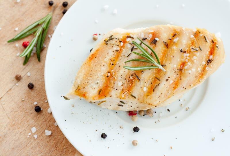 烤鸡胸脯用在白色板材的迷迭香 免版税库存照片