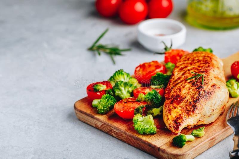 烤鸡胸脯用硬花甘蓝和蕃茄在木切板 免版税图库摄影