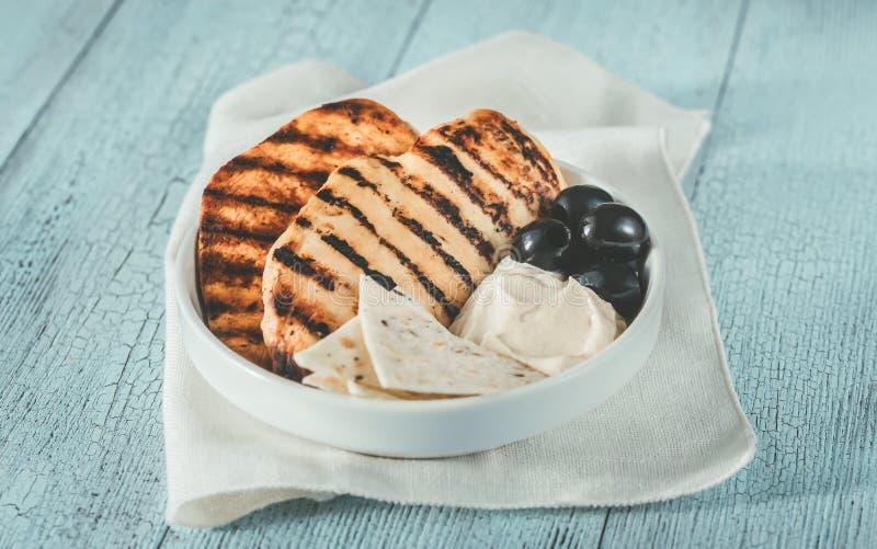 烤鸡胸脯用黑橄榄和tahini调味汁 库存图片