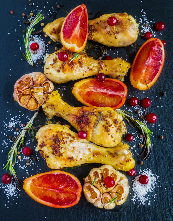 烤鸡腿、红色桔子、蔓越桔、大蒜和迷迭香在黑背景 免版税库存照片