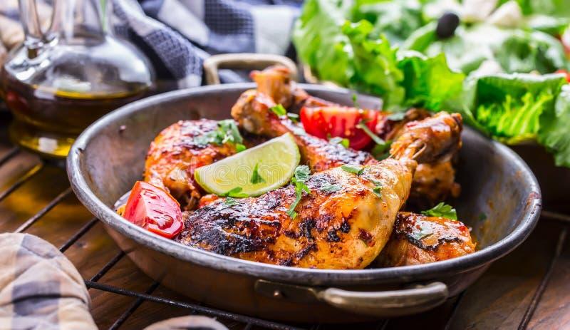 烤鸡腿、莴苣和西红柿limet橄榄 传统的烹调 地中海烹调 库存图片