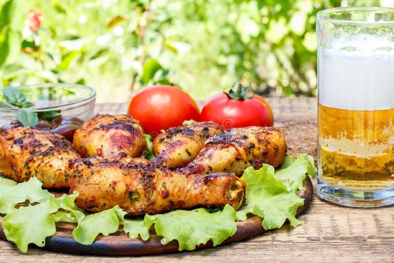 烤鸡腿和莴苣叶子在木砧板 库存图片