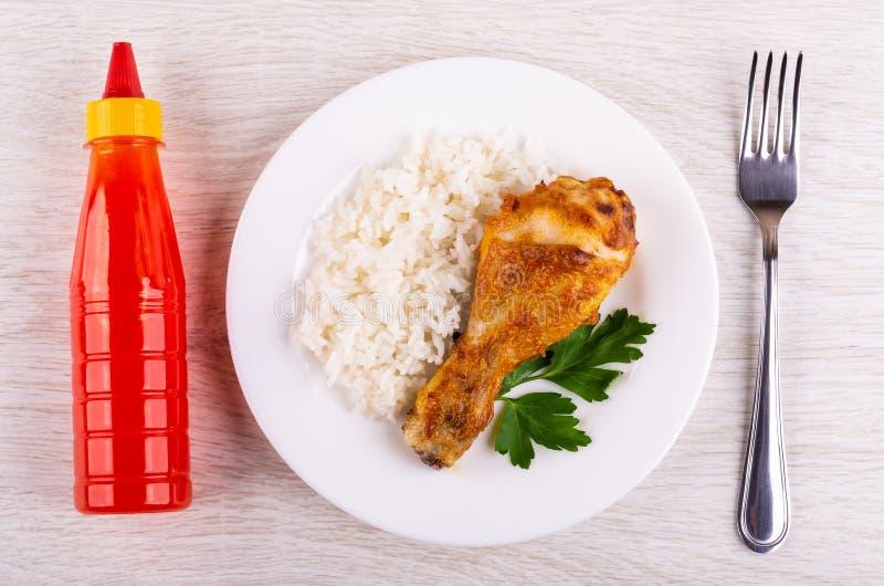 烤鸡腿用在板材,瓶的米番茄酱,在桌上的叉子 顶视图 库存图片