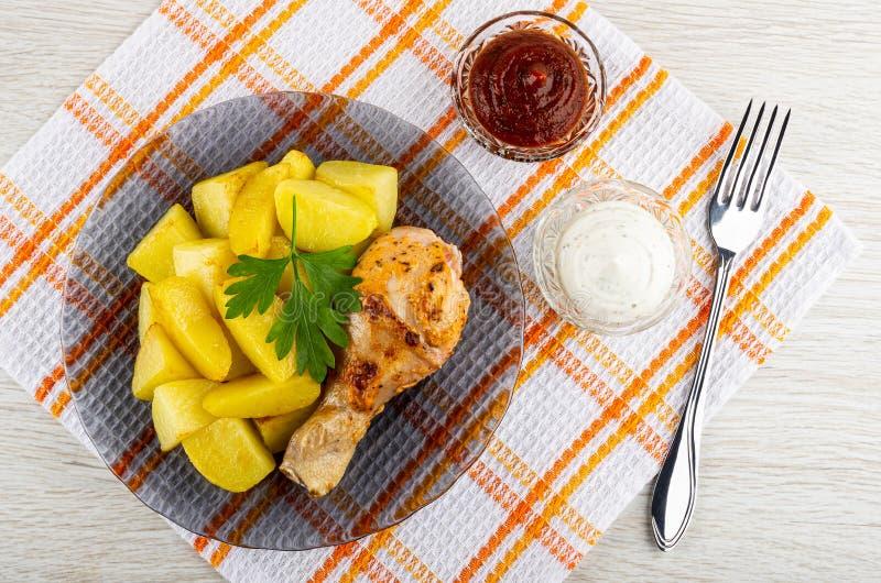 烤鸡腿用在灰色板材、番茄酱和蛋黄酱,在餐巾的叉子的油煎的土豆在木桌上 r 图库摄影