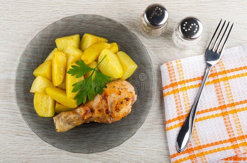 烤鸡腿用在灰色板材、番茄酱和蛋黄酱,在餐巾的叉子的油煎的土豆在木桌上 r 免版税库存图片