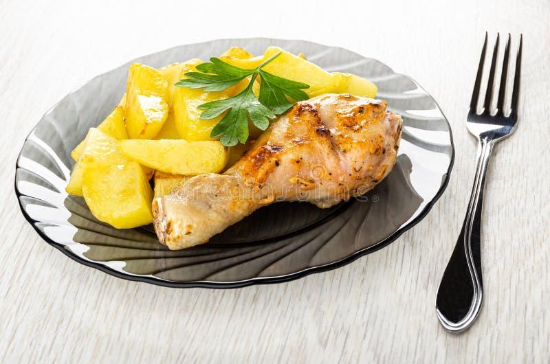 烤鸡腿用在灰色板材,在木桌上的叉子的油煎的土豆 库存图片