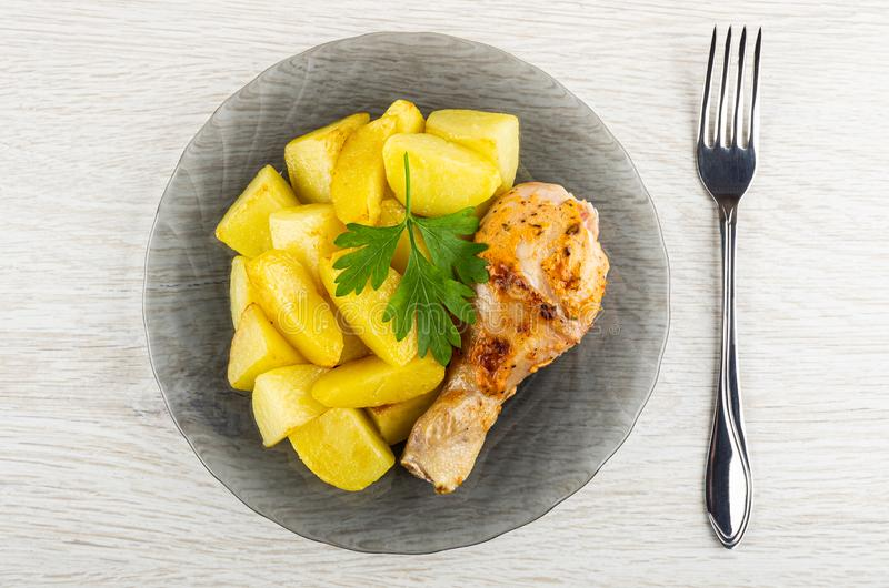 烤鸡腿用在灰色板材,在木桌上的叉子的油煎的土豆 r 库存图片