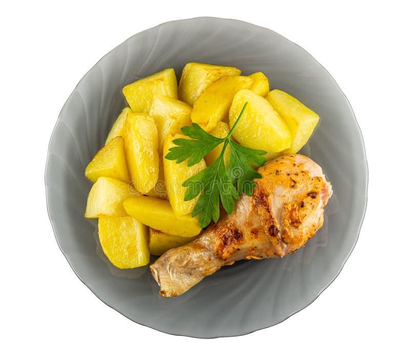 烤鸡腿用在白色隔绝的灰色板材的油煎的土豆 r 免版税库存图片