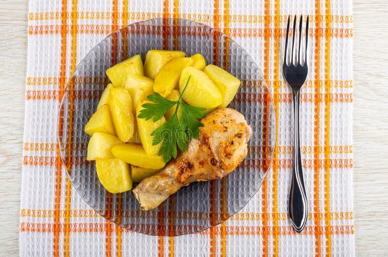 烤鸡腿用在透明板材,在餐巾的叉子的油煎的土豆在木桌上 r 库存照片