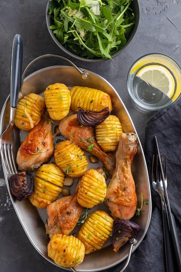 烤鸡腿用煮沸的土豆和菜在黑背景 复制空间 顶视图 免版税库存图片
