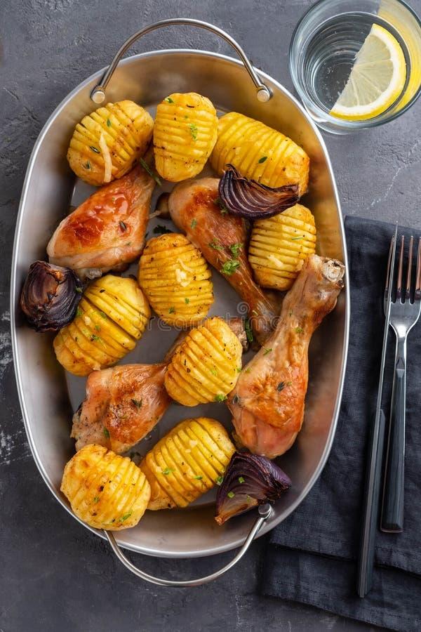 烤鸡腿用煮沸的土豆和菜在黑背景 复制空间 顶视图 库存照片