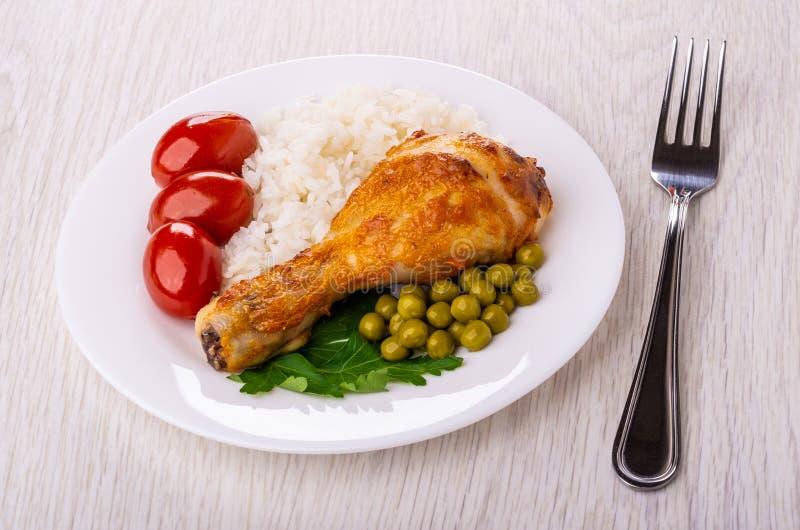 烤鸡腿用米,蕃茄,在板材,在桌上的叉子的绿豆 库存图片