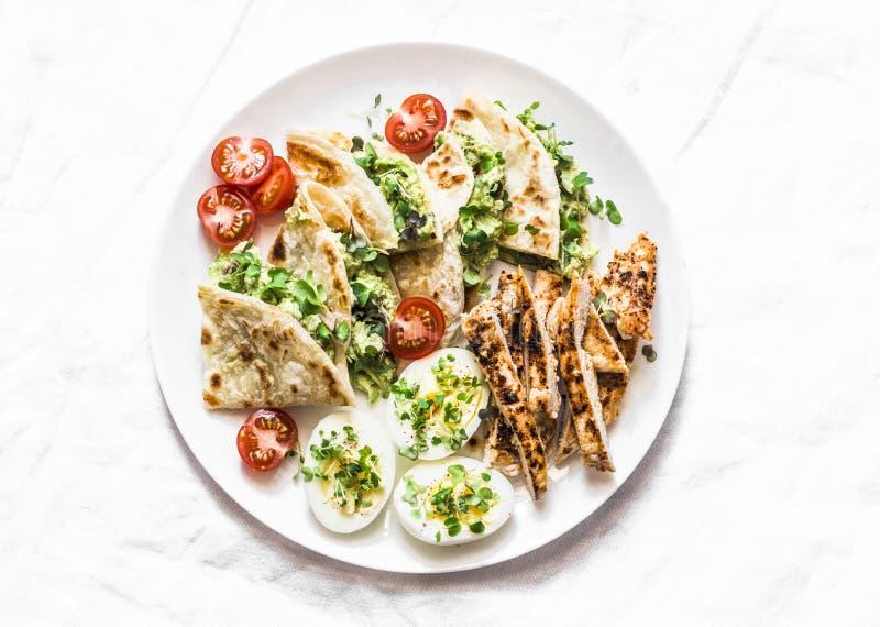 烤鸡,鲕梨奶油奶酪油炸玉米粉饼,熟蛋,菜-可口快餐,开胃菜,在光的塔帕纤维布 免版税图库摄影